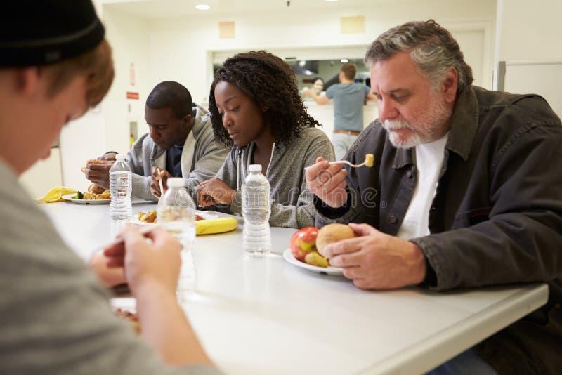 坐在表上的人们吃在流浪者避身处的食物 免版税库存照片