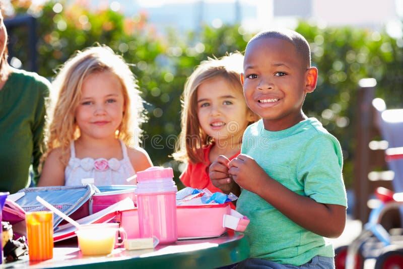 坐在表上的基本的学生吃午餐 免版税图库摄影