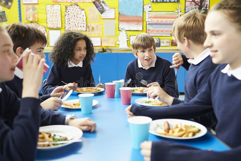 坐在表上的学童吃煮熟的午餐 免版税图库摄影