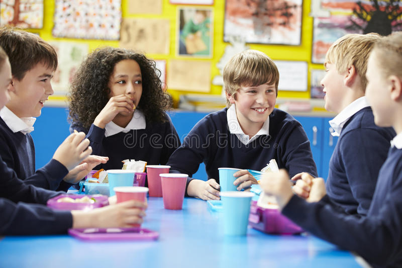 坐在表上的学童吃被包装的午餐 库存图片