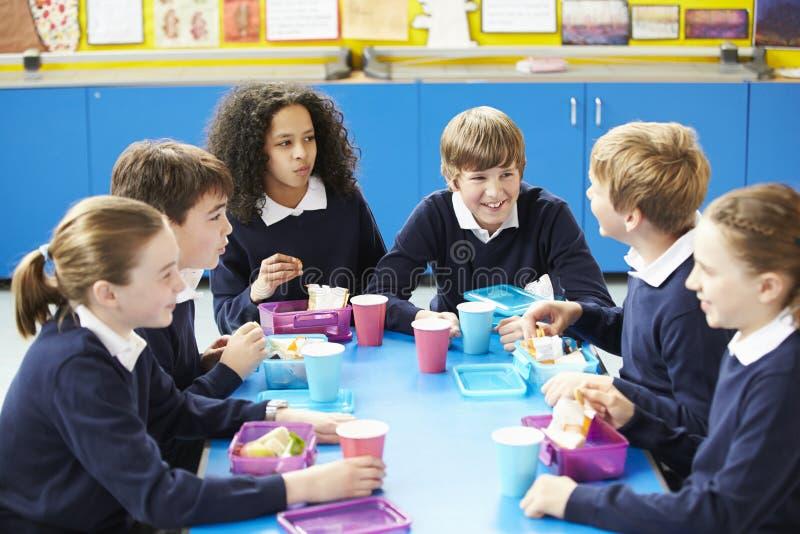 坐在表上的学童吃被包装的午餐 免版税库存图片