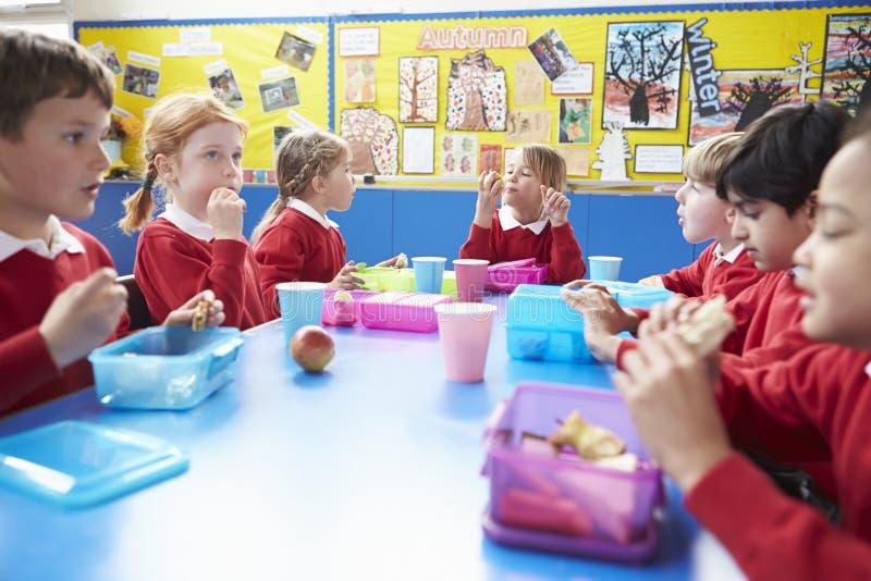 坐在表上的学童吃被包装的午餐 免版税库存照片