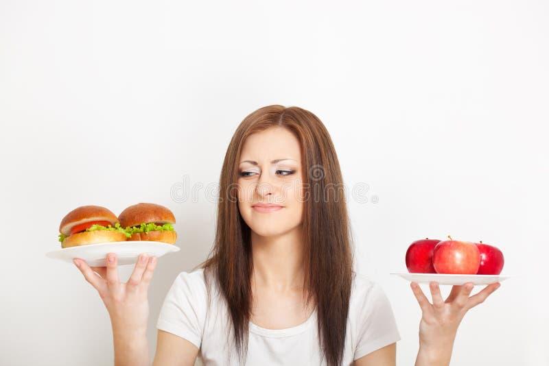 坐在表之后的妇女用食物 免版税库存照片