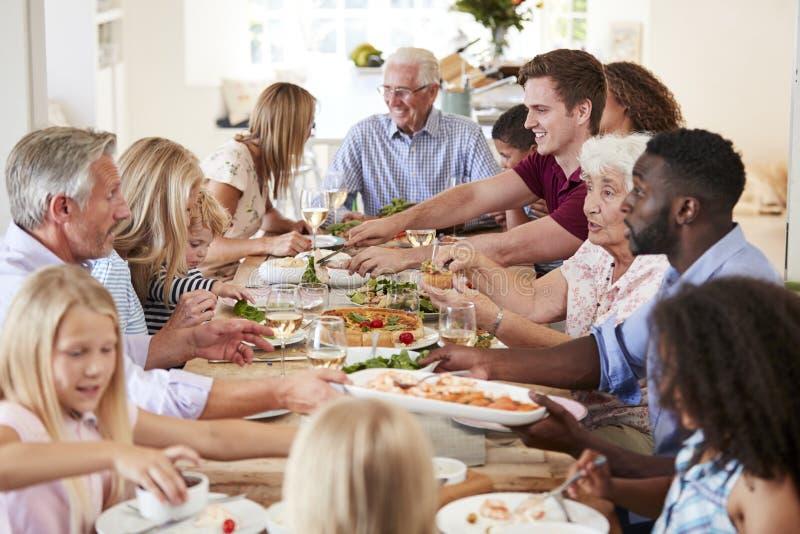 坐在表附近和享受膳食的小组多代的家庭和朋友 免版税库存图片
