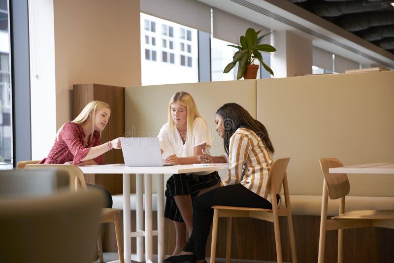 坐在表附近和合作在任务的小组年轻女实业家使用膝上型计算机 库存照片