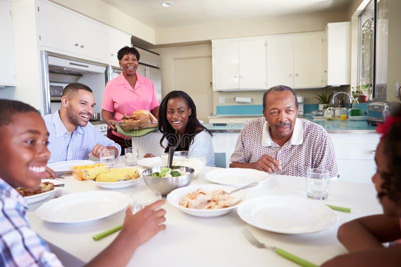 坐在表附近的多代的家庭吃膳食 免版税库存照片