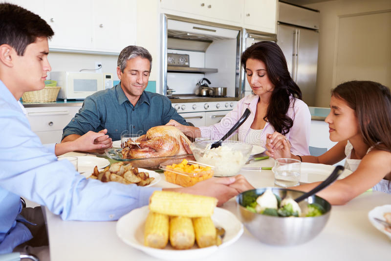 坐在表附近的家庭说祷告在吃膳食前 库存照片