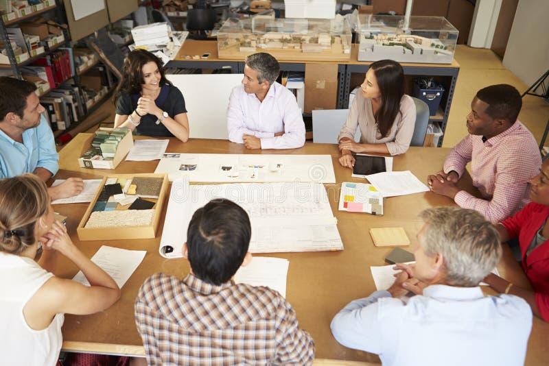 坐在表附近的小组建筑师开会议 免版税库存照片