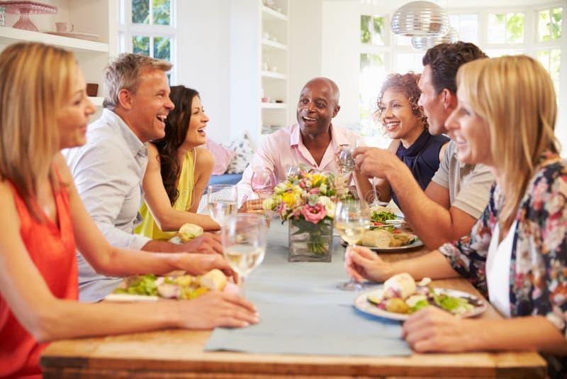 坐在表附近的成熟朋友在晚餐会 免版税库存照片