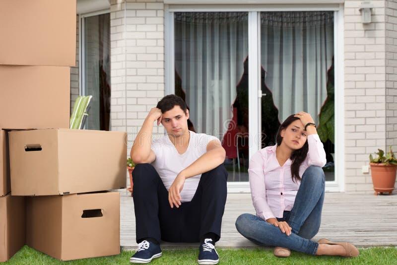 坐在被堆积的纸板箱附近的生气夫妇 免版税图库摄影