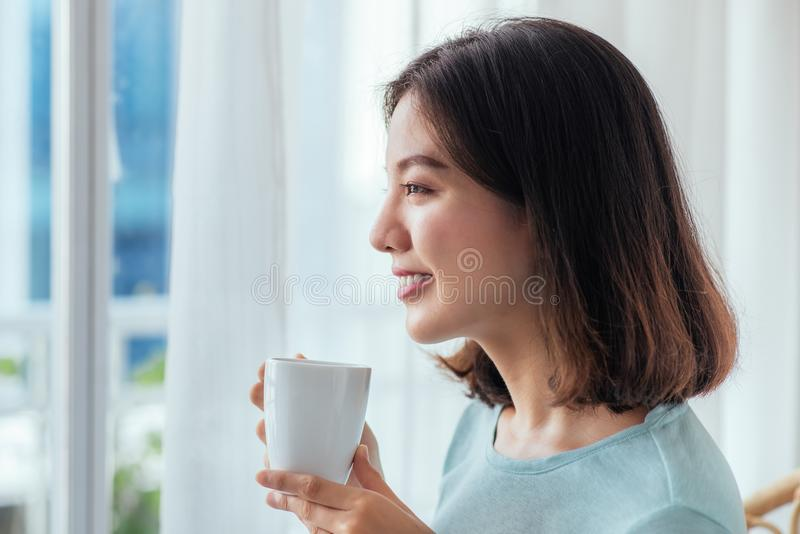 坐在被打开的窗口饮用的咖啡的年轻俏丽的妇女和 库存图片
