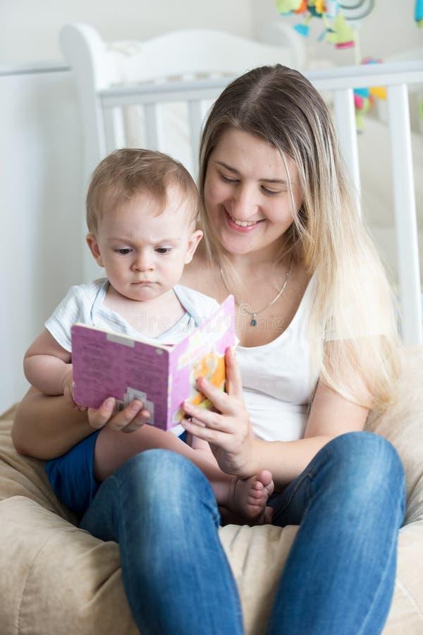 坐在装豆子小布袋和阅读书的美丽的微笑的母亲 图库摄影