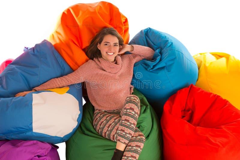 坐在装豆子小布袋椅子之间的年轻逗人喜爱的妇女 库存照片