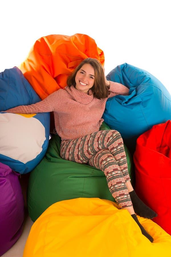 坐在装豆子小布袋椅子之间的年轻逗人喜爱的微笑的妇女 免版税图库摄影