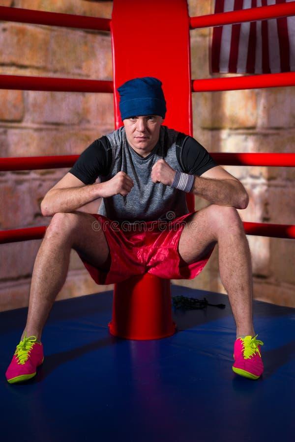 坐在规则b附近的红色角落的运动年轻男性拳击手 免版税图库摄影