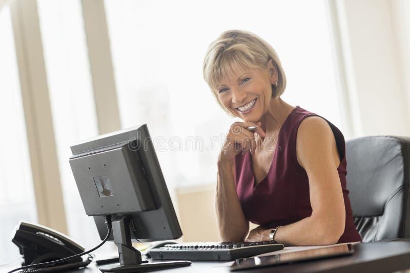 坐在计算机书桌的愉快的成熟女实业家 免版税库存图片
