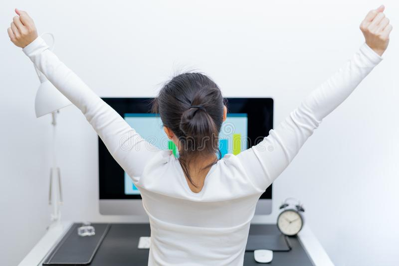 坐在计算机前面的年轻亚裔美丽的妇女和在长工作以后舒展自己 重音自由和放松 库存照片