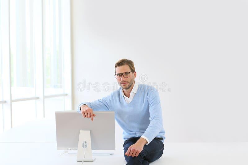 坐在计算机旁边的年轻商人 免版税库存图片