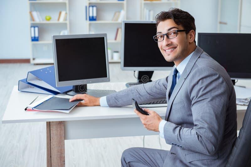 坐在许多屏幕前面的商人 库存图片