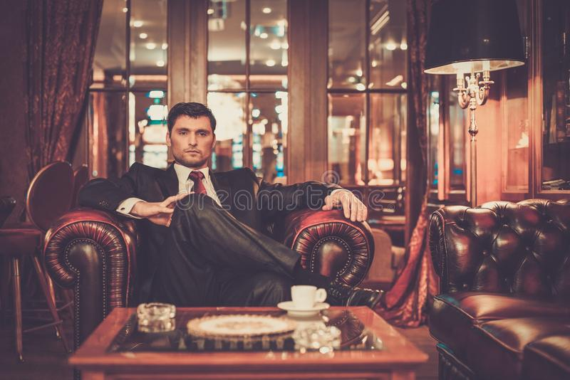 坐在豪华内部的英俊的人 免版税库存照片