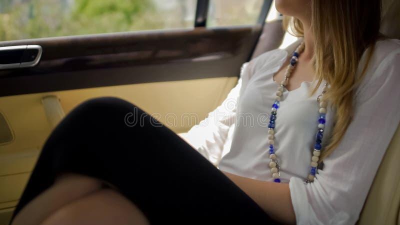 坐在豪华汽车和享受风景,期待已久的假期的富有的妇女 免版税图库摄影
