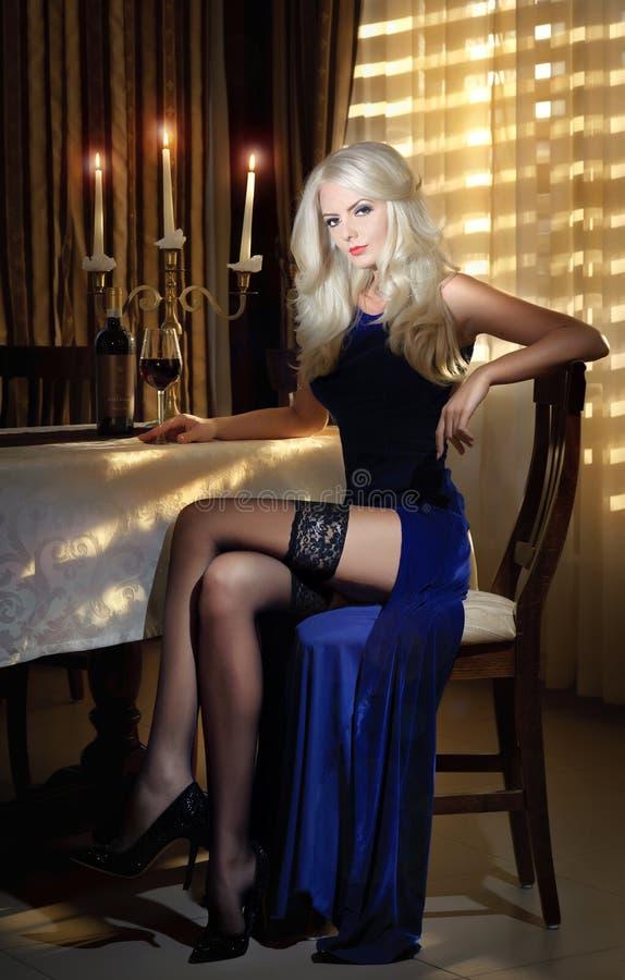 坐在豪华经典内部的一张桌附近的典雅的长的礼服的可爱的白肤金发的妇女。华美的白肤金发的模型 免版税图库摄影