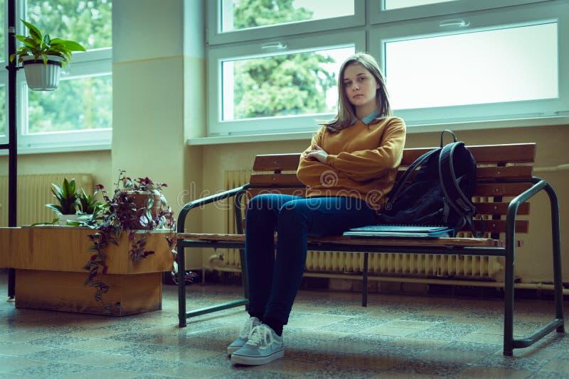 坐在走廊的年轻急切和沮丧的女性大学生在她的学校 教育,胁迫,消沉,重音 免版税图库摄影