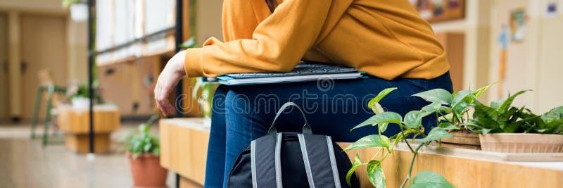 坐在走廊的年轻无法认出的沮丧的孤独的女性大学生在她的学校 教育,胁迫,消沉 免版税库存照片