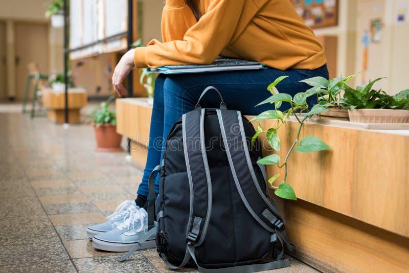 坐在走廊的年轻无法认出的沮丧的孤独的女性大学生在她的学校 免版税图库摄影
