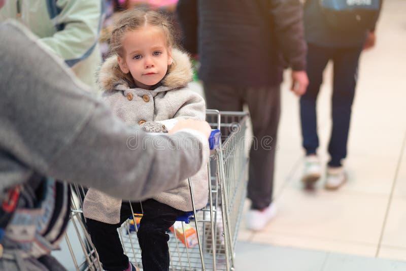 坐在超级市场台车和浏览照相机的女孩 免版税库存照片