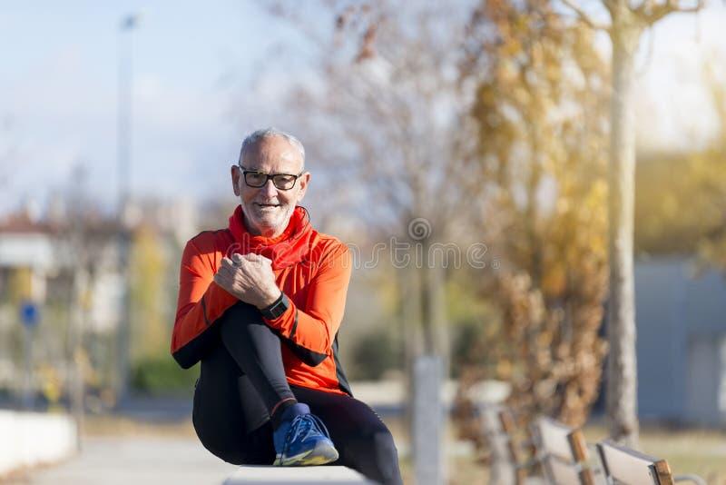 坐在跑步以后的资深赛跑者人 免版税库存照片