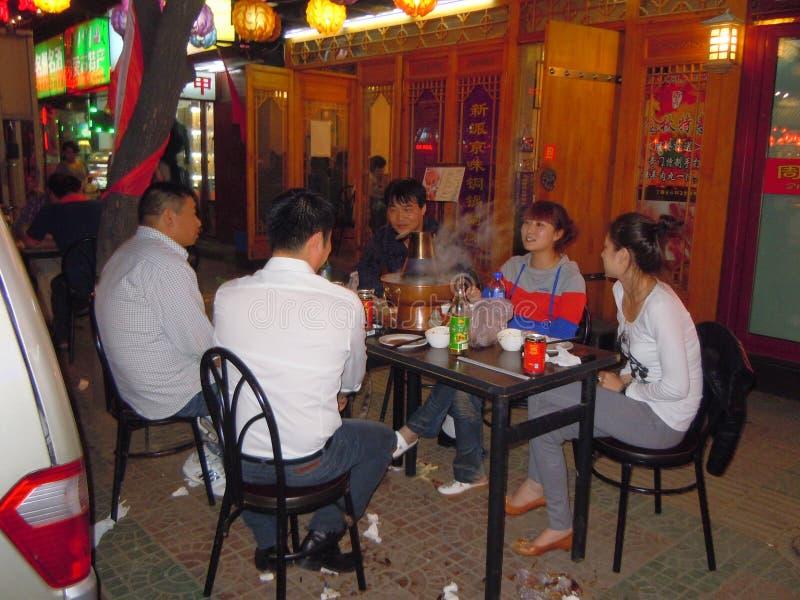 坐在路面咖啡馆的人们在晚上 库存图片