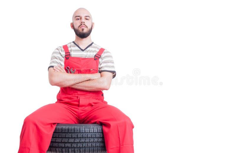 坐在车轮顶部的骄傲的技工 免版税库存图片