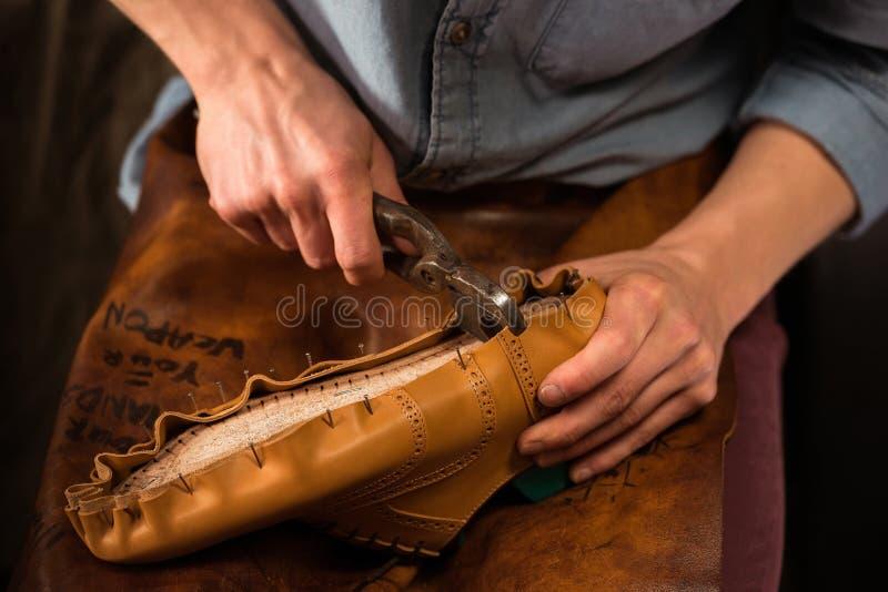 坐在车间的鞋匠做鞋子 免版税库存照片