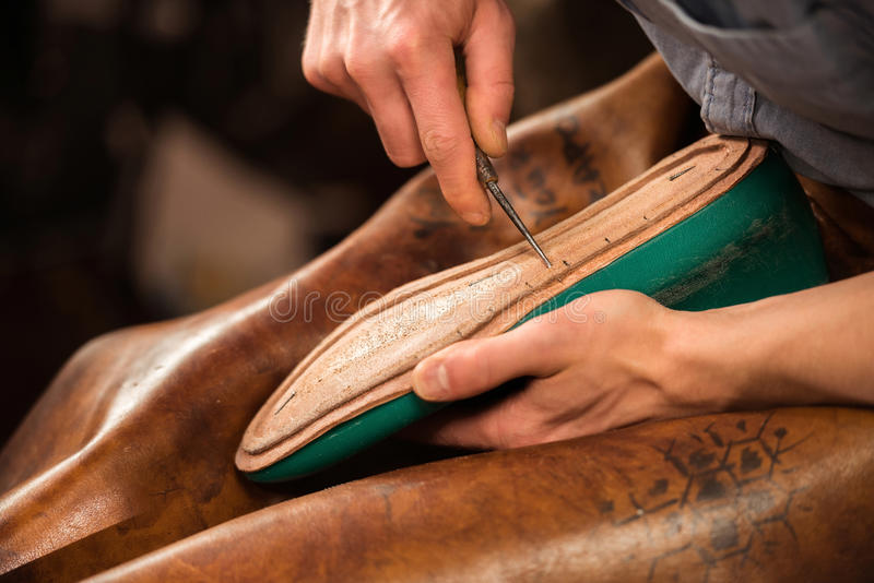 坐在车间的靴匠做鞋子 免版税库存图片