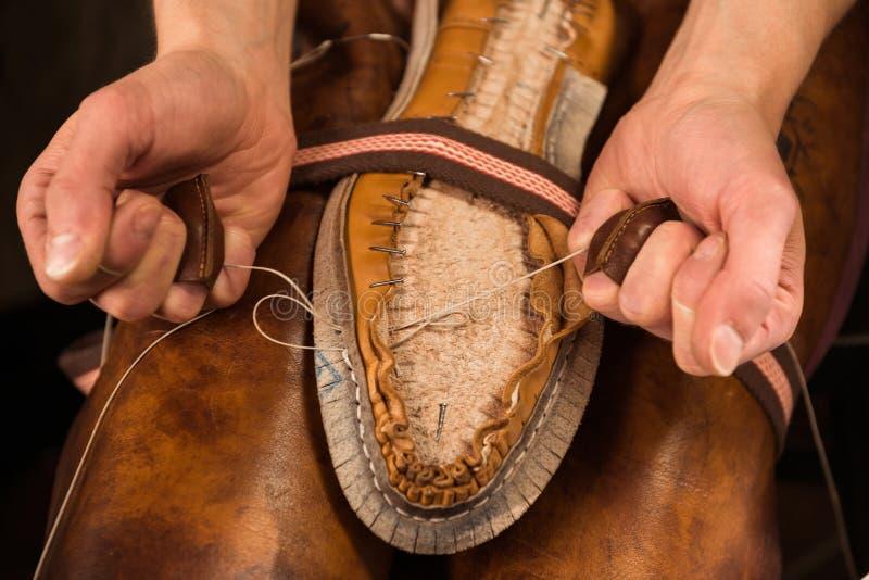 坐在车间的靴匠做鞋子 免版税图库摄影