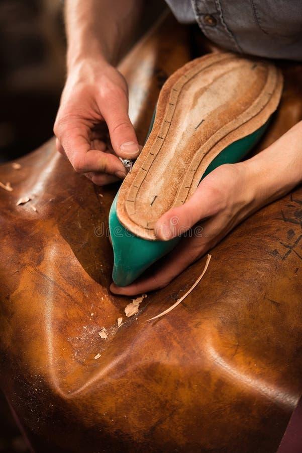 坐在车间的靴匠做鞋子 图库摄影