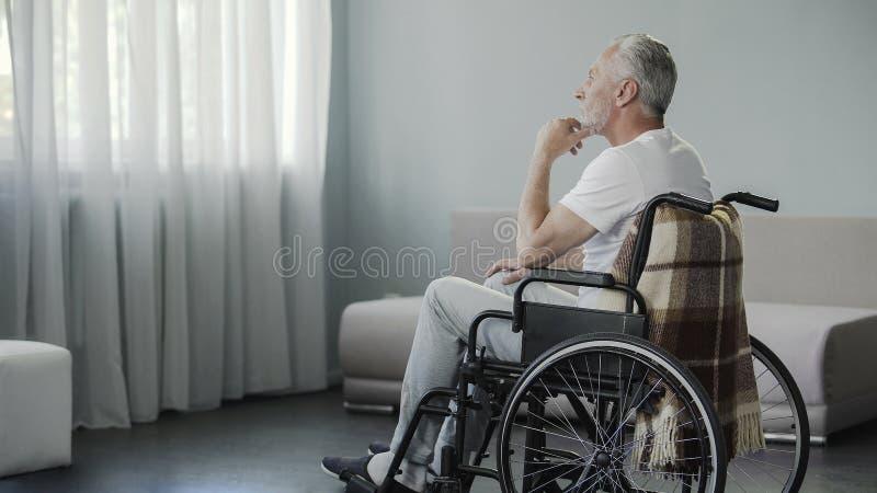 坐在轮椅和看在窗口,疾病的周道的退休的男性 库存图片