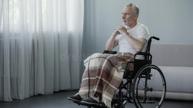 坐在轮椅和看在窗口,等待的家庭的资深残疾人 免版税图库摄影