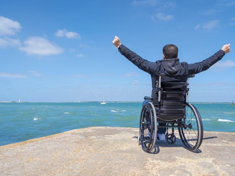 坐在轮椅和神色的残疾年轻人在海 免版税库存照片