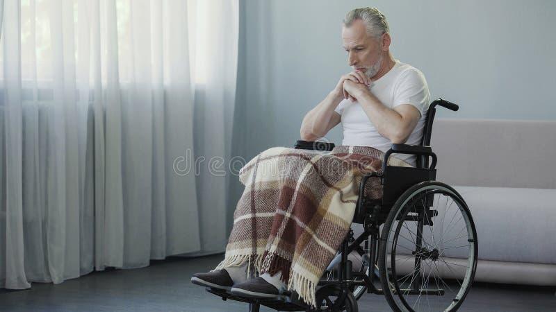 坐在轮椅和考虑生活,消沉的残疾人 免版税库存照片