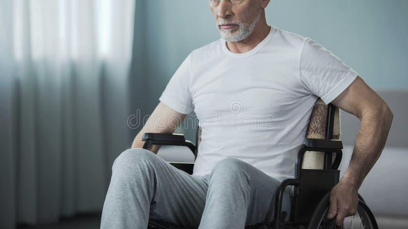 坐在轮椅回到照相机和看在窗口的孤独的人 免版税库存照片