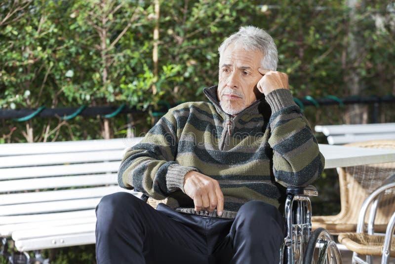 坐在轮椅的体贴的资深男性患者在草坪 免版税图库摄影