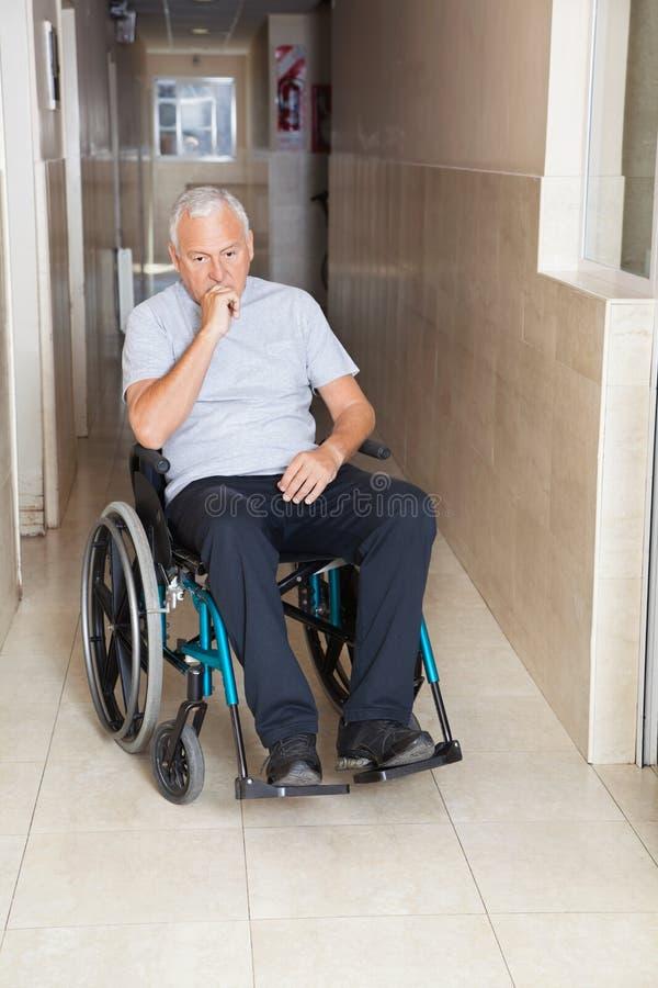 坐在轮椅的哀伤的老人 免版税库存图片