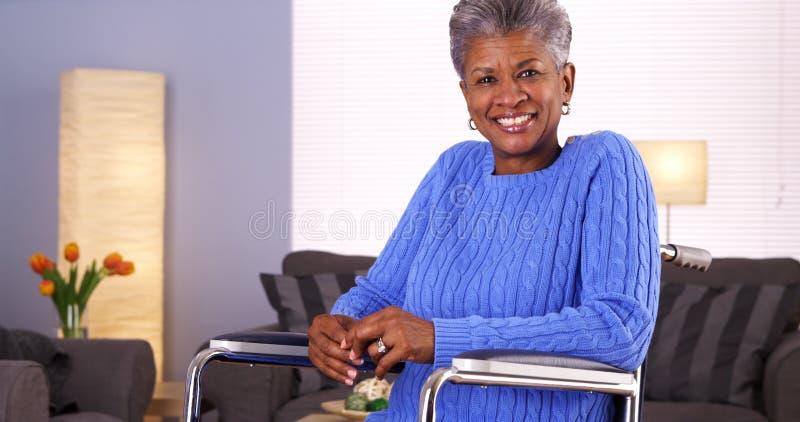 坐在轮椅的愉快的资深黑人妇女 免版税库存图片