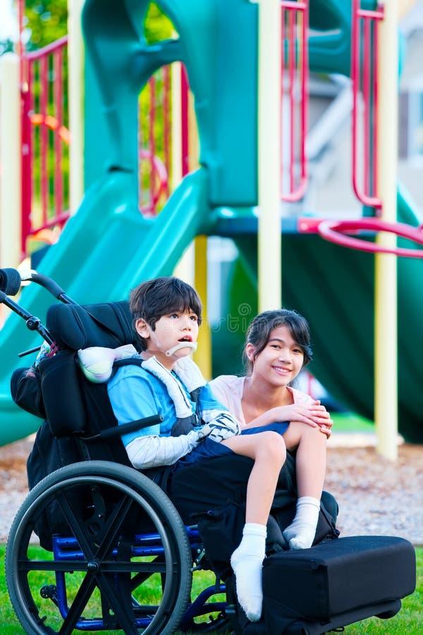 坐在轮椅的残疾兄弟旁边的姐妹在playgro 免版税库存图片