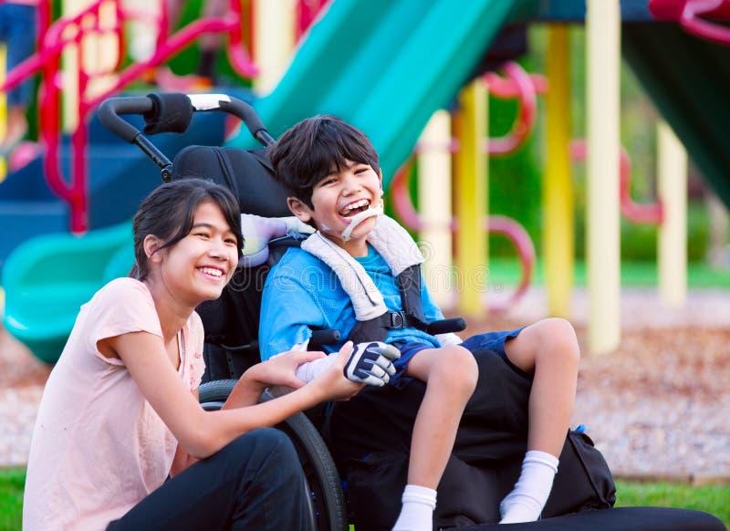 坐在轮椅的残疾兄弟旁边的姐妹在playgro 库存图片