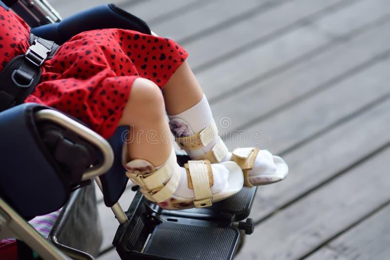 坐在轮椅的残疾女孩 在她的腿整直法 儿童大脑麻痹 ?? 库存图片
