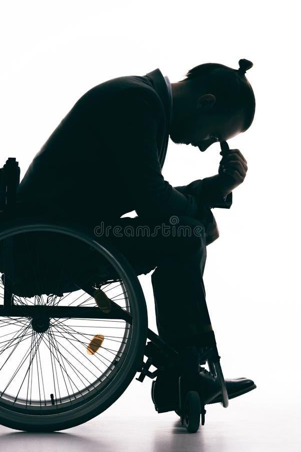 坐在轮椅的沮丧的人剪影 免版税库存照片