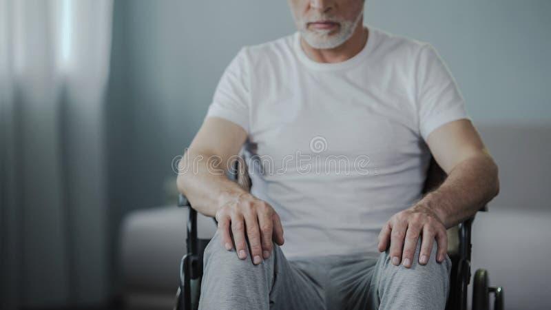 坐在轮椅的男性,考虑他的生活在康复中心 免版税库存照片